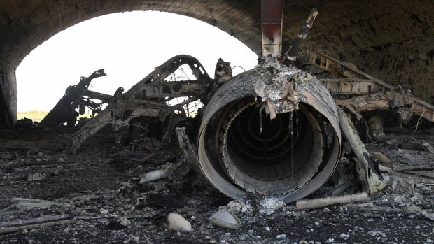 The aftermath: a plane destroyed in the US missile attack on a Syrian air base.