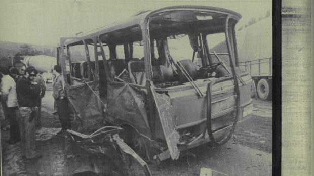 A policeman and other people look at a military bus that was destroyed after a bomb, which was placed in a parked car, ...