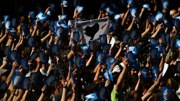 Pro-independence Basque followers hold up the symbol of the day called 'Artisans of the Peace', during a meeting after ...