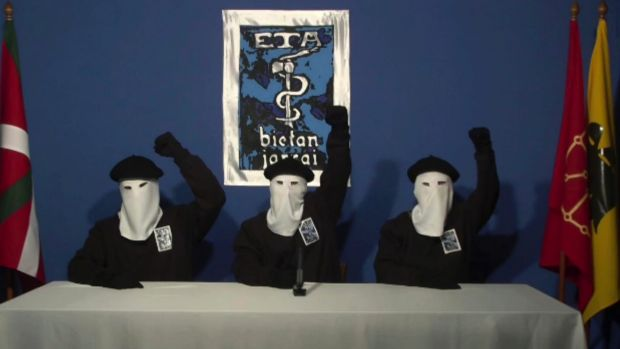 In this file image made from video provided in October, 2011, masked members of the Basque separatist group ETA raise ...