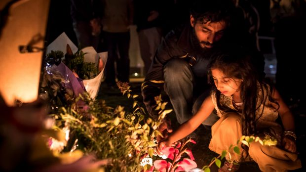 Adnan Amjid, friend and housemate of Zeeshan Akbar, helps a girl light a candle at a vigil.