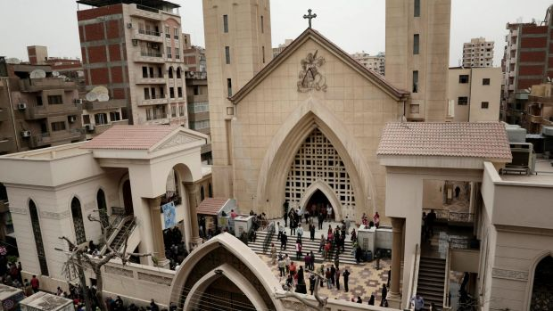 People gather outside the St. George's Church after a deadly suicide bombing, in the Nile Delta town of Tanta, Egypt.