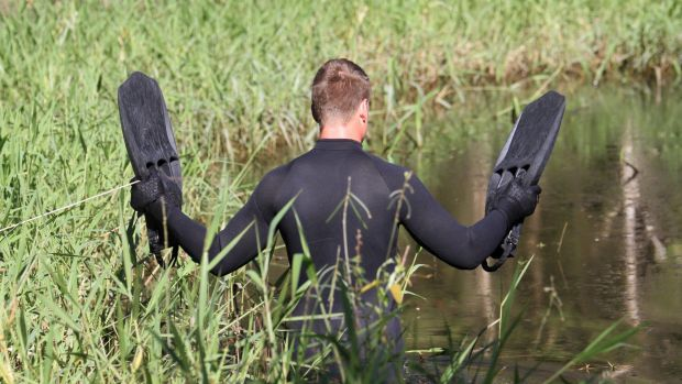 Divers from the police and the ADF search Deagon Wetlands for clues in the Youngkin investigation.