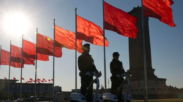 Chinese police officers patrol on motorised platforms on Tiananmen Square