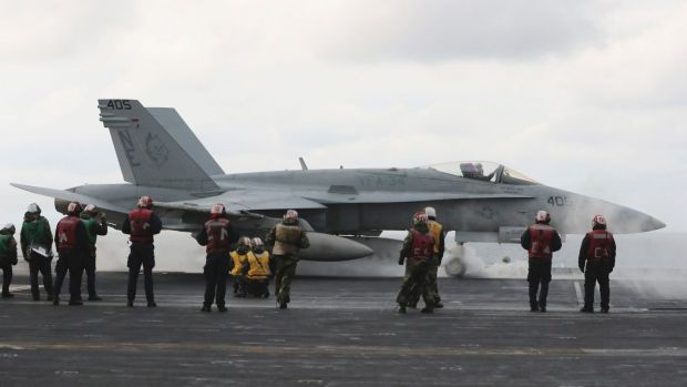 An F/A-18 fighter prepares to take off from the deck of the aircraft carrier USS Carl Vinson at an unidentified location ...
