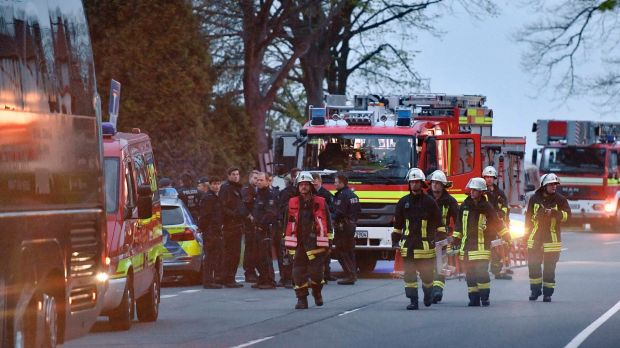 Police officers and firefighters stand outside the Dortmund team bus after it was damaged in an explosion.