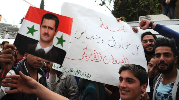 """Pro-government protesters hold a portrait of President Basharal- Assad and a placard that reads, """"Down with everyone who ..."""