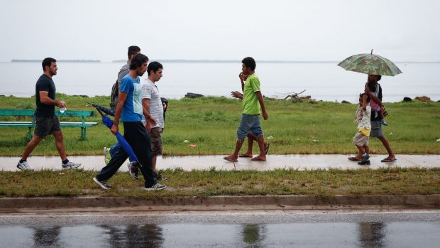 Asylum seekers walk past locals on Manus Island. The conditions at the detention centre have been exposed repeatedly.