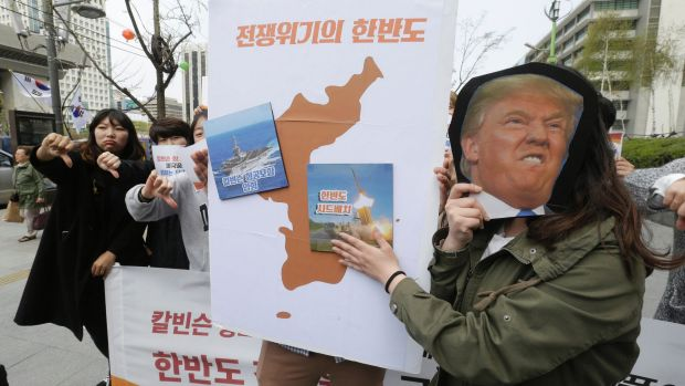 A South Korean protester holds a mask of US President Donald Trump and a Korean Peninsula map during a rally against US ...