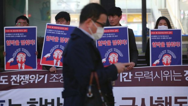 A man walks past a group of South Koreans protesting against US President Donald Trump near the US embassy in Seoul on ...