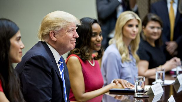 US President Donald Trump, left, smiles while meeting with women small business owners.