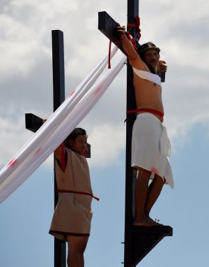 Reuben Enaje (right cross) playing the role of Jesus during the Passion Play a re-enactment of Christs crucifixion, on ...