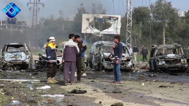 Rebel gunmen at the site of a blast that damaged several buses and vans.
