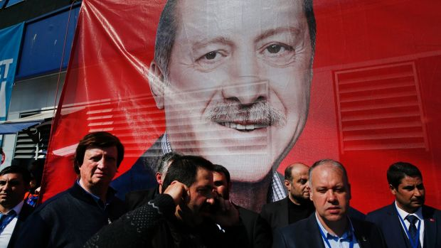 "Supporters of the ""Yes"" campaign stand in front of a giant picture of Turkish President Recep Tayyip Erdogan."