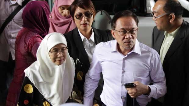 Malaysia's opposition leader Anwar Ibrahim, second from right, arrives with his wife Wan Azizah for the verdict in his ...
