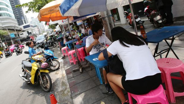 Lunch time: People eat noodles at a street food stall on Thonglor road, Bangkok, Thailand. Officials see street food as ...