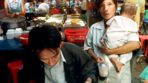 A woman begs for money or food from a diner while holding a baby in Bangkok.
