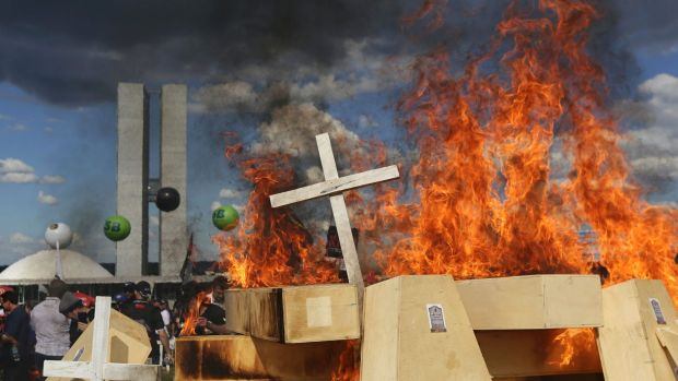 Striking police officers set fire to coffins during a protest against pension reforms outside Congress in Brasilia, on ...