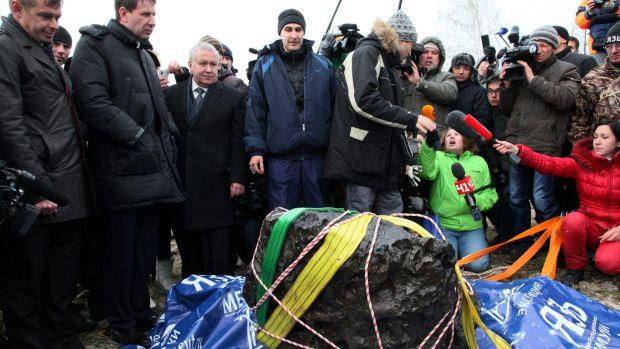 People look at what scientists believe to be a chunk of the Chelyabinsk meteor, which exploded over Russia in 2013.