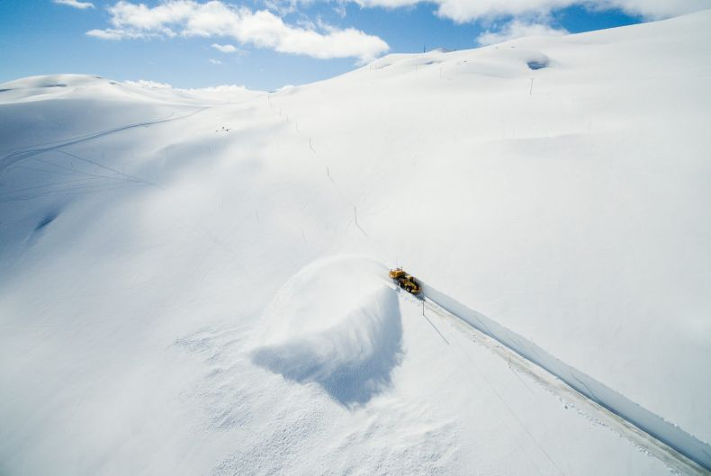 A powerful snowblower works, in spectacular surroundings on the road crossing the Sognefjellet mountain between the east ...