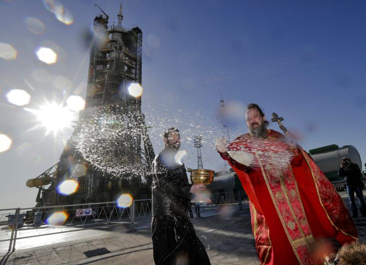 An Orthodox priest conducts a blessing service in front of the Soyuz FG rocket at the Russian leased Baikonur ...