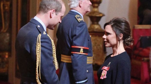 Fashion designer Victoria Beckham receives her OBE from Britain's Prince William, the Duke of Cambridge during an ...