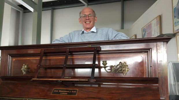 Tuner Martin Backhouse with the piano where he found a stash of gold.