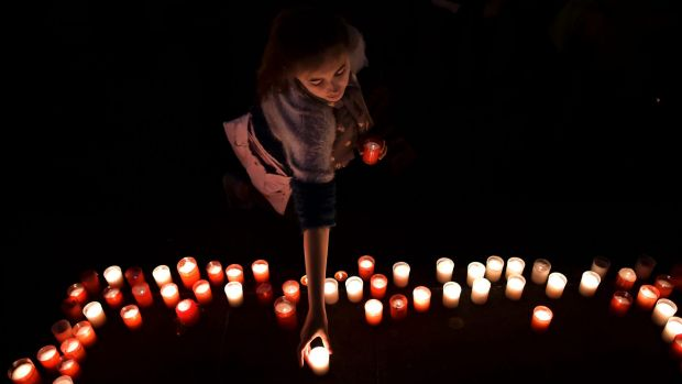 A girl places a candle in tribute last year for the people who died in the attack on Guernica.