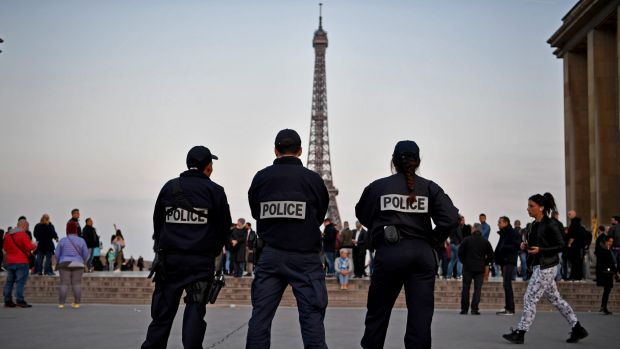 On guard: Police officers secure the Place du Trocedero the day after a gunman opened fire on police at the Champs Elysees.