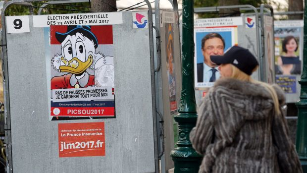 A woman looks at a poster with the Disney character Uncle Scrooge fixed over the official poster of French presidential ...