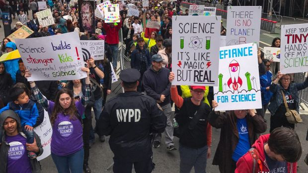 Demonstrators pass a policeman in the March for Science in New York last week.