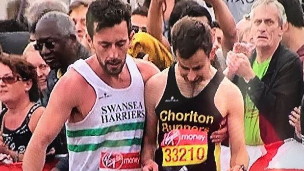 Matthew Rees, left, helps David Wyeth in the final stages of the London Marathon.