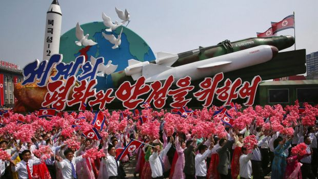 North Koreans wave as they march next to a float display of models of different missiles during a military parade in ...