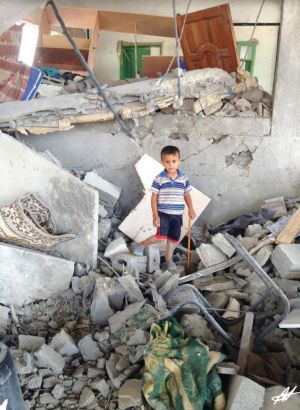 A boy in occupied Palestine stands in what remains of his bedroom after an air strike.