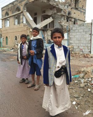 Boys from Yemen in their traditional dress stand in front of their bombed house.