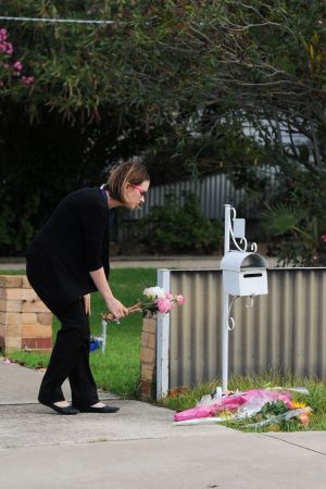 A well-wisher leaves flowers outside the home where Ora Holt and Greg Floyd died.