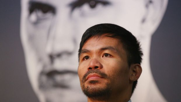 He's behind you: Manny Pacquiao speaks to the media as a picture of Jeff Horn looms over him.