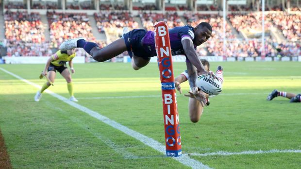 Flying high: Melbourne winger Suliasi Vunivalu gets airborne to score against the Dragons.