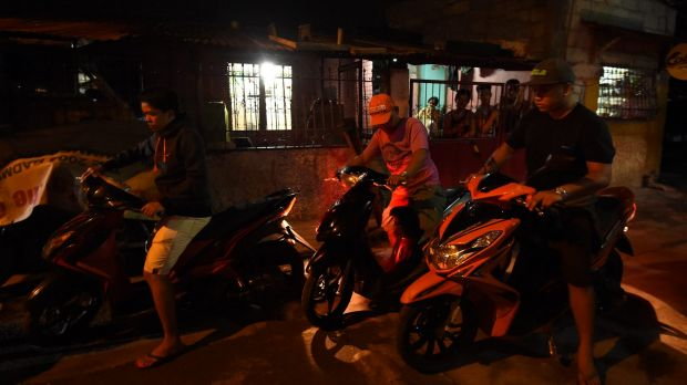 Police on motorbikes leave the scene where three men were slain in a drug related killing in Caloocan, Manila, ...