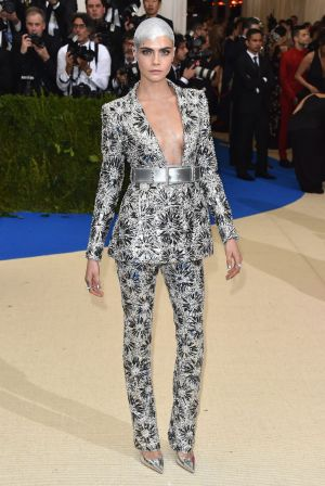 After shaving her hair for a movie role, Cara Delevingne took to the Met Gala with an incredible silver design on her ...