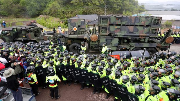 South Korean police protect a US military vehicle from protesters who oppose a plan to deploy the THAAD system against ...