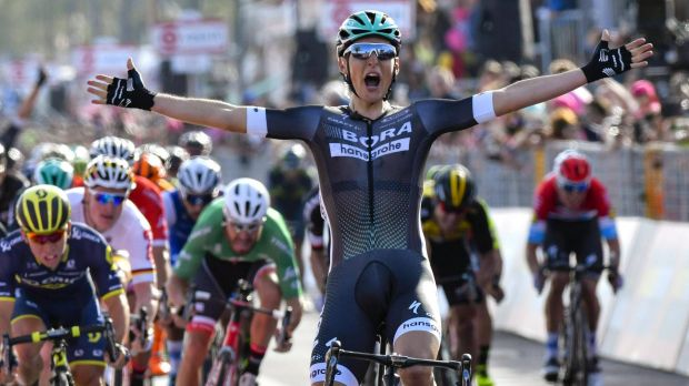 Austria's Lukas Poestelberger celebrates as he crosses the finish line to win the first stage of the Giro d'Italia.