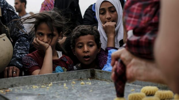 Children stare at a baker baking fresh cookies at a food distribution point in western Mosul, Iraq. Thousands of people ...