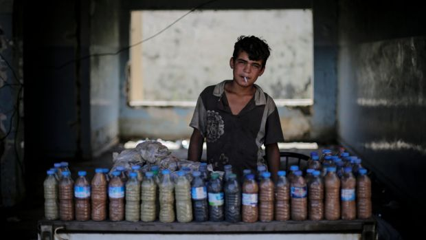 Abdul Aziz, 15, smokes a cigarette while waiting for customers to buy the mud from a sulphur well near the Hamam Alil ...