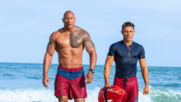 Buff daddy: Dwayne Johnson and Zac Efron in the movie reboot of <i>Baywatch</i>.
