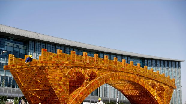 Workers install a 'Golden Bridge of Silk Road' structure outside revealed at the time of China's Belt and Road Forum in ...