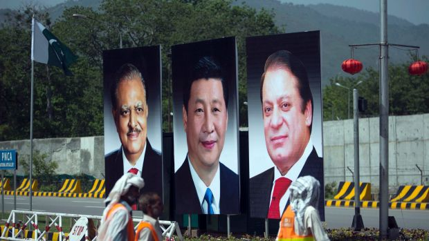 Workers walk past a billboard showing pictures of Chinese President Xi Jinping, centre, with Pakistani President Mamnoon ...