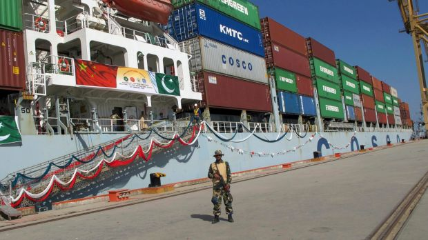 A Pakistan Navy soldier stands guard while a loaded Chinese ship prepares to depart from Gwadar port.
