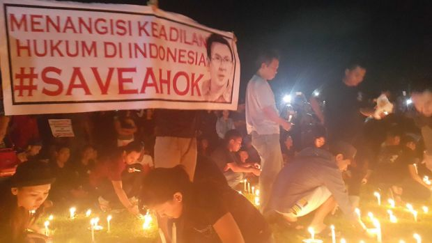 """At a candlelit vigil in Bali, the sign reads """"Bitter over the lack of justice in Indonesian law""""."""