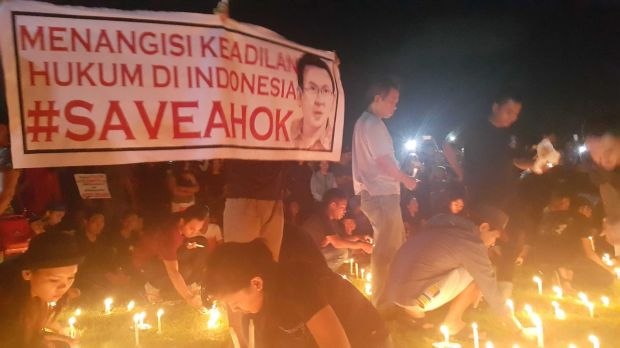 "Supporters conduct a candlelit vigil in Bali in support of Ahok. The sign reads ""Bitter over the lack of justice in ..."